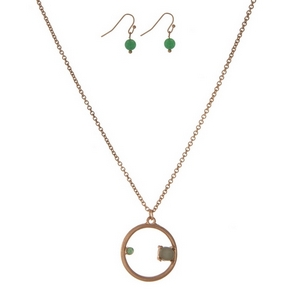 "Dainty gold tone necklace set with a circle pendant, accented with a rhinestone and a green stone. Approximately 16"" in length."