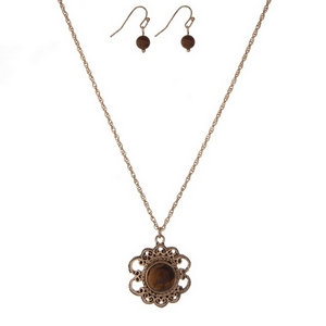"Dainty gold tone necklace set with a flower pendant, accented by a brown stone and matching fishhook earrings. Approximately 16"" in length."