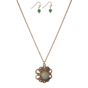 """Dainty gold tone necklace set with a flower pendant, accented by a green stone and matching fishhook earrings. Approximately 16"""" in length."""