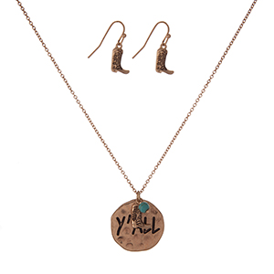 "Gold tone necklace set with a circle pendant stamped with ""Y'all"" and accented with a boot charm and matching fishhook earrings. Approximately 16"" in length."