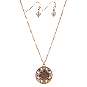 "Dainty gold tone necklace set with a circle pendant, accented by a gray stone and matching fishhook earrings. Approximately 16"" in length."