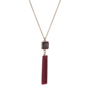 "Gold tone necklace with a burgundy natural stone pendant, accented by a gray rhinestone. Approximately 32"" in length."