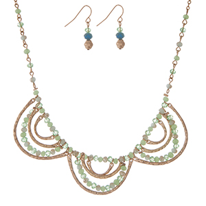 "Gold tone necklace set with light green beads, a scalloped design, and matching fishhook earrings. Approximately 16"" in length."