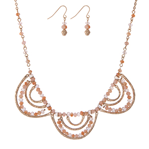 "Gold tone necklace set with peach and champagne beads, a scalloped design, and matching fishhook earrings. Approximately 16"" in length."