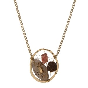 """Gold tone necklace displaying a wire wrapped oval pendant with assorted natural and wooden stones and a topaz rhinestone. Approximately 32"""" in length."""