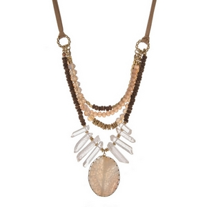 Brown suede necklace displaying layers of brown wooden beads, peach faceted beads, white crystals and an ivory natural stone. Necklace can be tied at any length up to 32.""