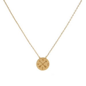 "Dainty gold tone necklace featuring a round brushed pendant with a stamped compass and arrows. Pendant approximately 7mm. Length adjusts from 16""-18""."