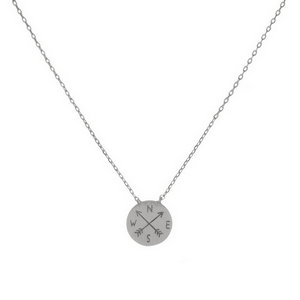 """Dainty silver tone necklace featuring a round brushed pendant with a stamped compass and arrows. Pendant approximately 7mm. Length adjusts from 16""""-18""""."""