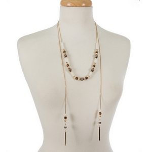 "Dainty gold tone wrap necklace featuring brown wooden and opal beads. Approximately 24"" and 36"" in length."
