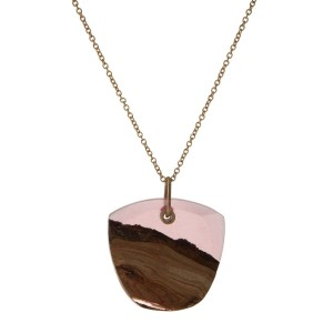 "Gold tone necklace featuring a wooden and pink resin pendant. Approximately 32"" in length."