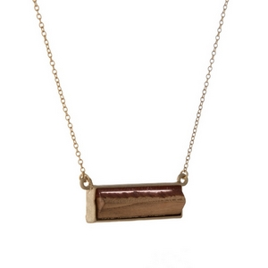 "Dainty gold tone necklace featuring a wooden and pink resin bar pendant. Approximately 16"" in length."