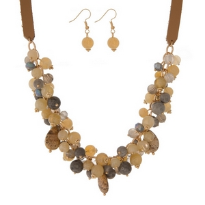 "Tan faux leather necklace set featuring tan, gray, and picture jasper beads and stones. Approximately 18"" in length."