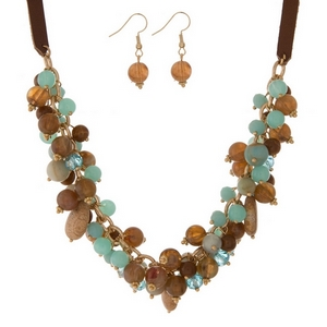 "Tan faux leather necklace set featuring brown, turquoise, and picture jasper beads and stones. Approximately 18"" in length."