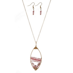 "Gold tone necklace set displaying an open teardrop shape with wire wrapped pink beads. Approximately 32"" in length."