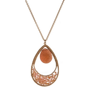 "Gold tone necklace with a peach natural stone and beaded teardrop pendant. Approximately 32"" in length."
