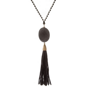 "Gray wooden and faceted beaded necklace featuring a gray natural stone pendant and fabric tassel. Approximately 32"" in length."
