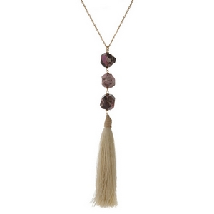"Gold tone necklace displaying three pink and brown natural stone beads and an ivory fabric tassel. Approximately 32"" in length."