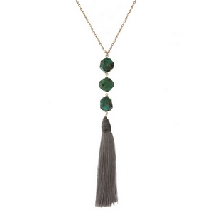 "Gold tone necklace displaying three turquoise natural stone beads and a gray fabric tassel. Approximately 32"" in length."