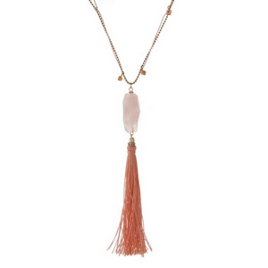 "Gold tone and pink cord necklace displaying a rose quartz natural stone pendant and a peach tassel. Approximately 32"" in length."