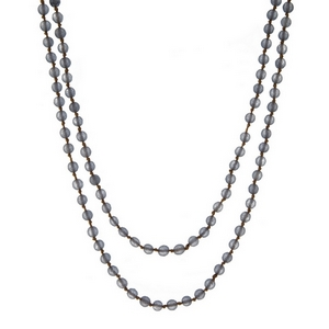 "Tan knotted cord wrap necklace displaying gray natural stone beads. Approximately 60"" in length."