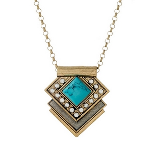 "Gold tone necklace featuring a geometric pendant with a turquoise stone and clear rhinestones. Approximately 28"" in length."