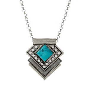 "Silver tone necklace featuring a geometric pendant with a turquoise stone and clear rhinestones. Approximately 28"" in length."