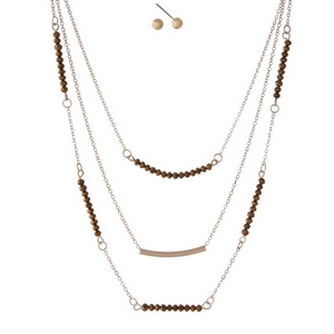 "Dainty gold tone, three layer necklace set featuring bronze beads, a curved bar pendant and matching stud earrings. Approximately 14"" to 18"" in length."