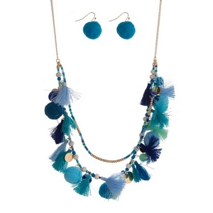 "Gold tone necklace featuring light blue, mint and royal blue tassels, beads and pom poms. Approximately 24"" in length."