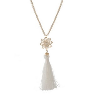 "Gold tone necklace featuring a flower pendant, white fabric tassel and ivory beaded accents. Approximately 30"" in length."