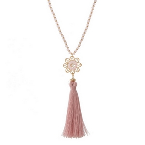 "Gold tone necklace featuring a flower pendant, pink fabric tassel and pink beaded accents. Approximately 30"" in length."