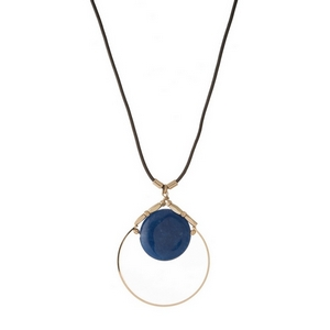 "Gray leather cord necklace featuring an open gold tone circle pendant with a blue natural stone. Approximately 32"" in length."