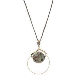 "Gray leather cord necklace featuring an open gold tone circle pendant with a sesame jasper natural stone. Approximately 32"" in length."