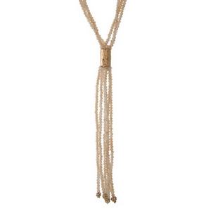 "Ivory and champagne beaded, multi strand necklace featuring a tassel pendant and gold tone accent. Approximately 26"" in length."