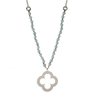 "Silver tone necklace featuring light blue natural stone beads and an open clover pendant. Approximately 32"" in length."
