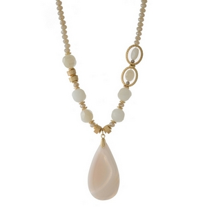 "Gold tone necklace featuring ivory faceted beads and an ivory natural stone pendant. Approximately 32"" in length."