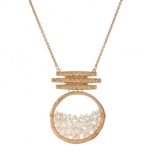 "Gold tone necklace featuring an ivory beaded circle pendant. Approximately 32"" in length."