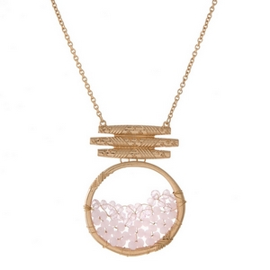 "Gold tone necklace featuring a pale pink beaded circle pendant. Approximately 32"" in length."