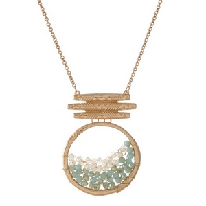 "Gold tone necklace featuring a mint green beaded circle pendant. Approximately 32"" in length."