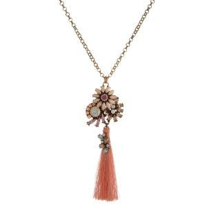 "Gold tone necklace with peach rhinestones and a fabric tassel. Approximately 28"" in length."