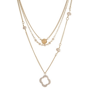 "Dainty gold tone, three layer necklace featuring freshwater pearl beads and a clover pendant. Approximately 16"" to 20"" in length."