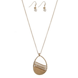 "Gold tone necklace set featuring a white beaded teardrop pendant and matching fishhook earrings. Approximately 32"" in length."