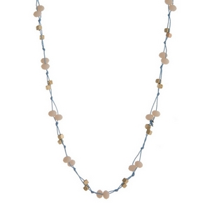 "Light blue cord necklace with ivory faceted beads and gold tone accents. Approximately 32"" in length."
