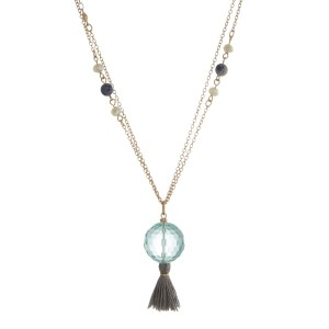 "Gold tone necklace featuring ivory faceted beads, a turquoise bead pendant and a gray tassel. Approximately 36"" in length."