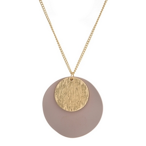 "Gold tone necklace with a brushed gold tone and a mauve circle pendant. Approximately 32"" in length."