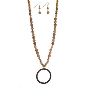 "Brown wooden and picture jasper natural stone beaded necklace set featuring an open circle pendant, gold tone accents and matching fishhook earrings. Approximately 34"" in length."