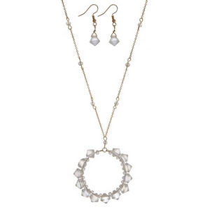 """Gold tone necklace set with a clear iridescent beaded circle pendant and matching fishhook earrings. Approximately 32"""" in length."""