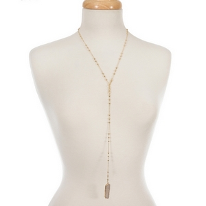 "Gold tone 'Y' necklace with an ivory natural druzy stone pendant. Approximately 22"" in length."
