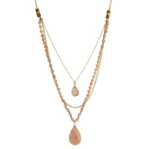 "Gold tone necklace featuring three layers, champagne and ivory beads, and a pale pink natural stone pendant. Approximately 28"" to 32"" in length."