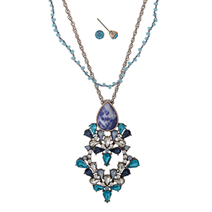 "Rose gold tone necklace set with a turquoise and blue rhinestone pendant and beaded accents. Approximately 18"" in length."