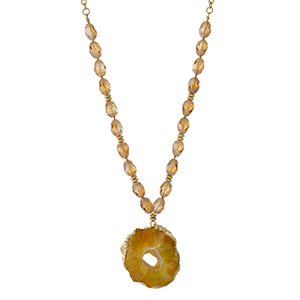"Gold tone necklace with topaz beads and an orange natural stone pendant. Approximately 32"" in length. Handmade in the USA."